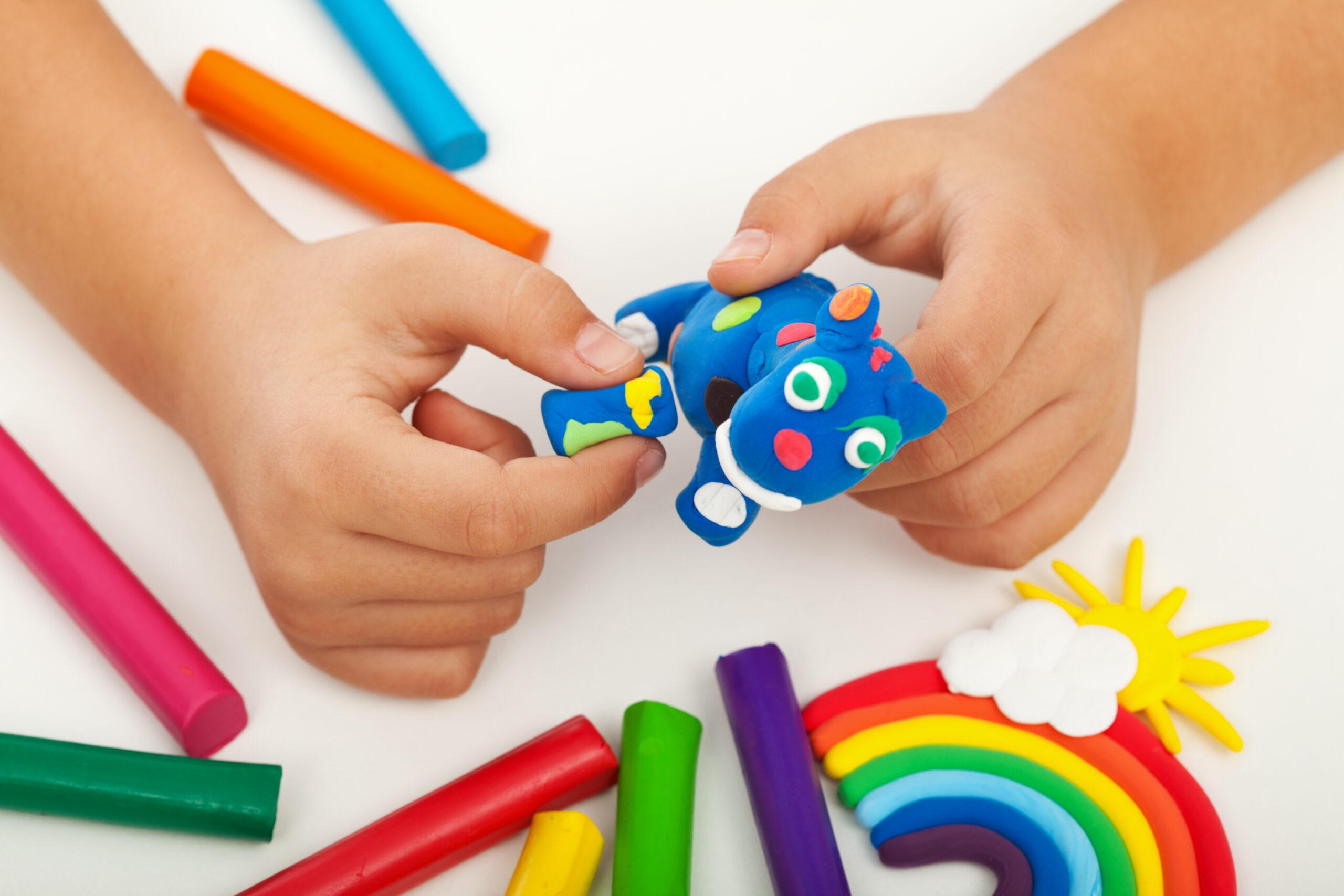 kinderhanden aan het knutselen met klei