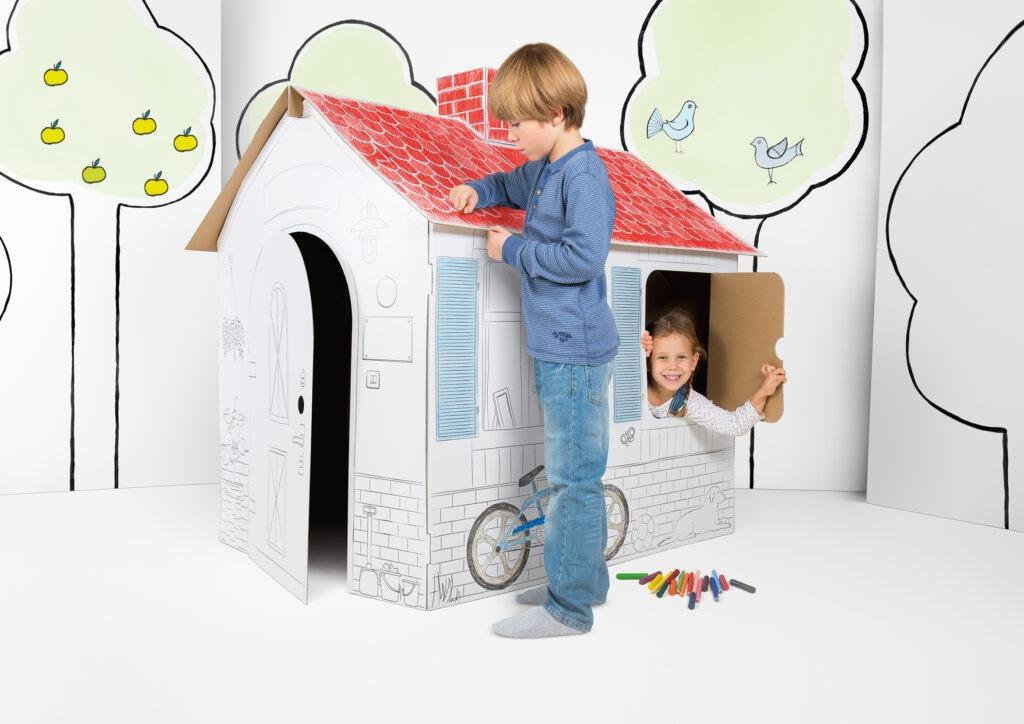 Kartonnen speelgoedhuisje wordt ingekleurd door kind