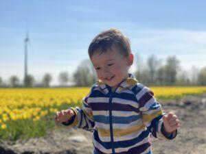 Jongen speelt in tulpenveld