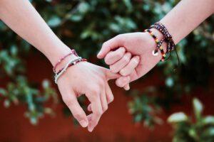 2 handen met kralenarmbandjes