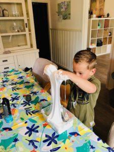 Hoe maak je zelf slijm? Jongen met handen in DIY slijm