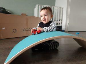 Kind speelt met auto op een wobbel